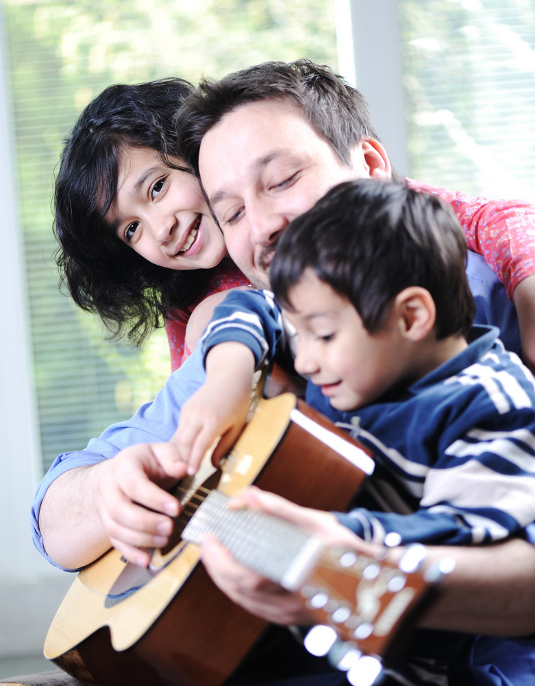 Happy family playing guitar together at home Royalty-Free