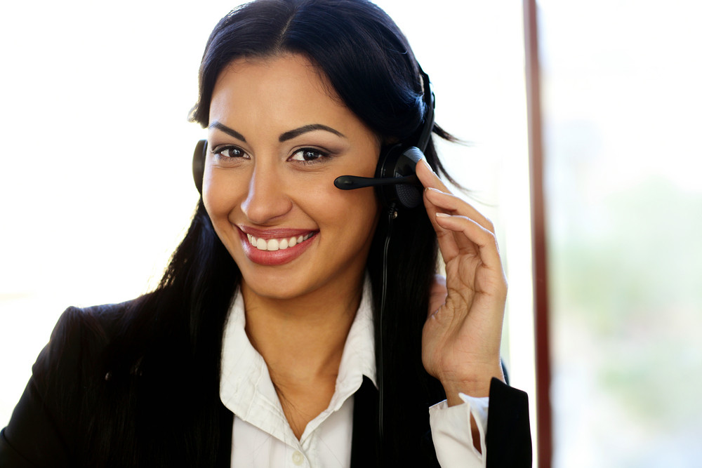 Happy female customer support operator with headset