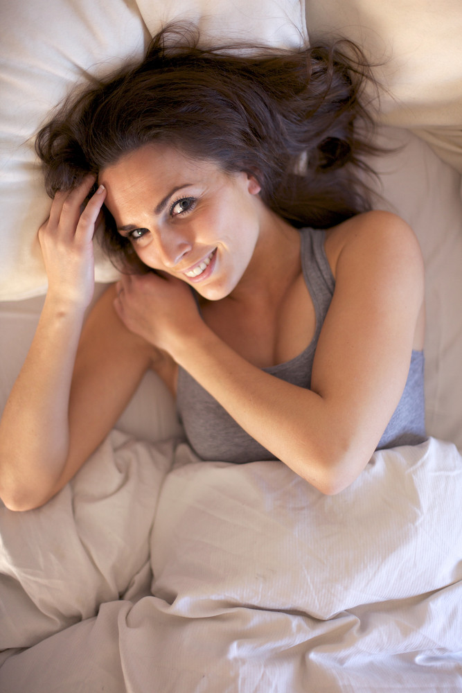 Happy indoor woman lying on bed smiling and looking at you
