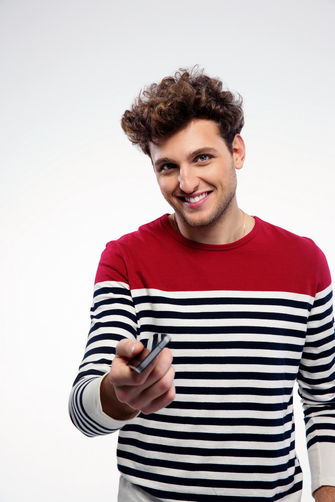 Happy man giving smartphone at you over gray background