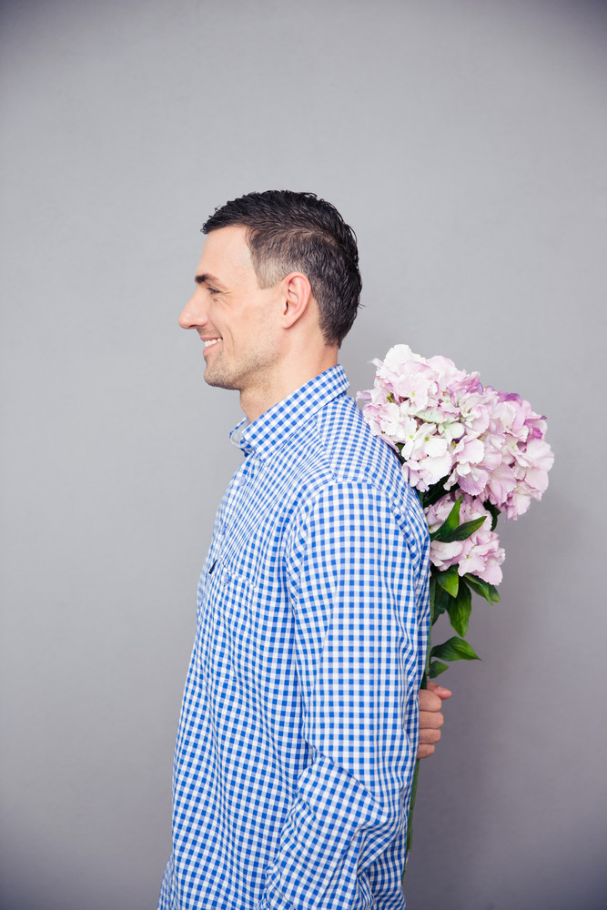 Happy man hiding flower behind his back