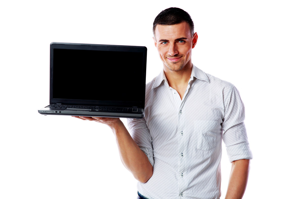 Happy man standing and holding laptop with blank screen over white background