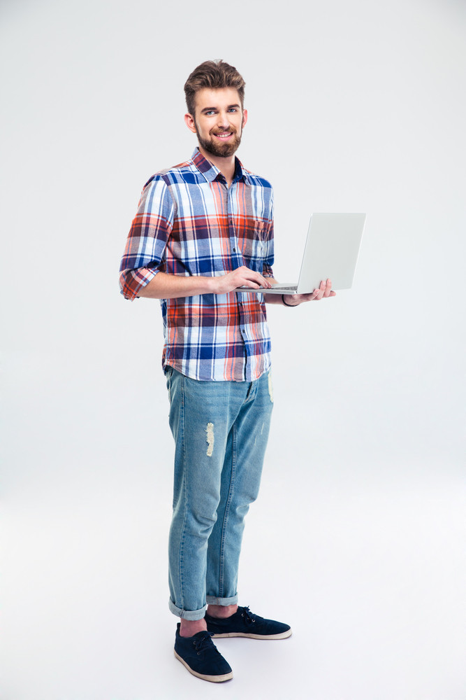 Happy man standing with laptop computer