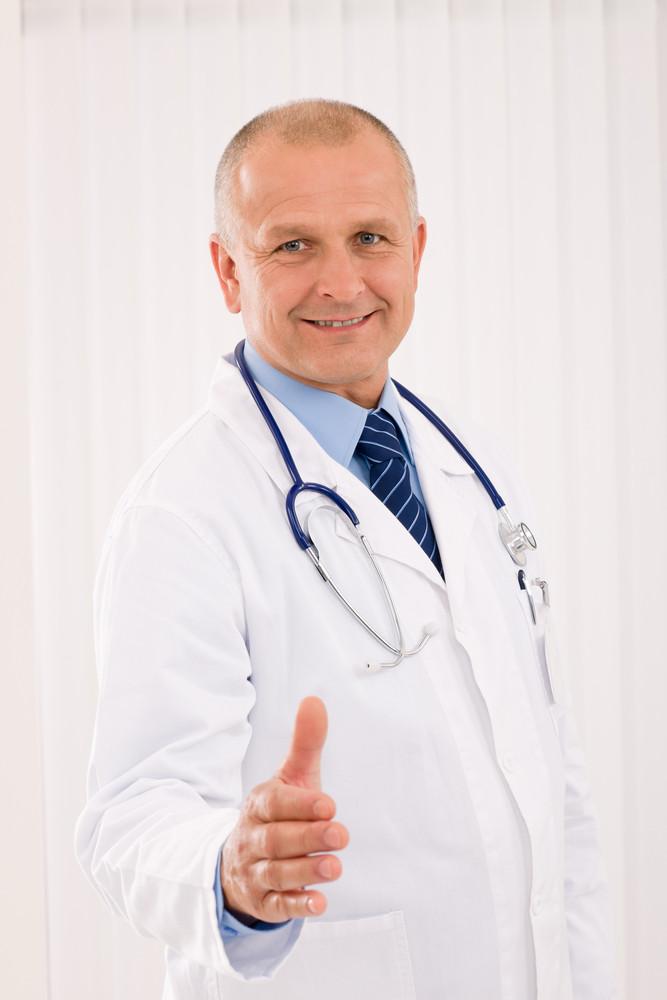 Happy mature doctor male giving handshake welcoming portrait