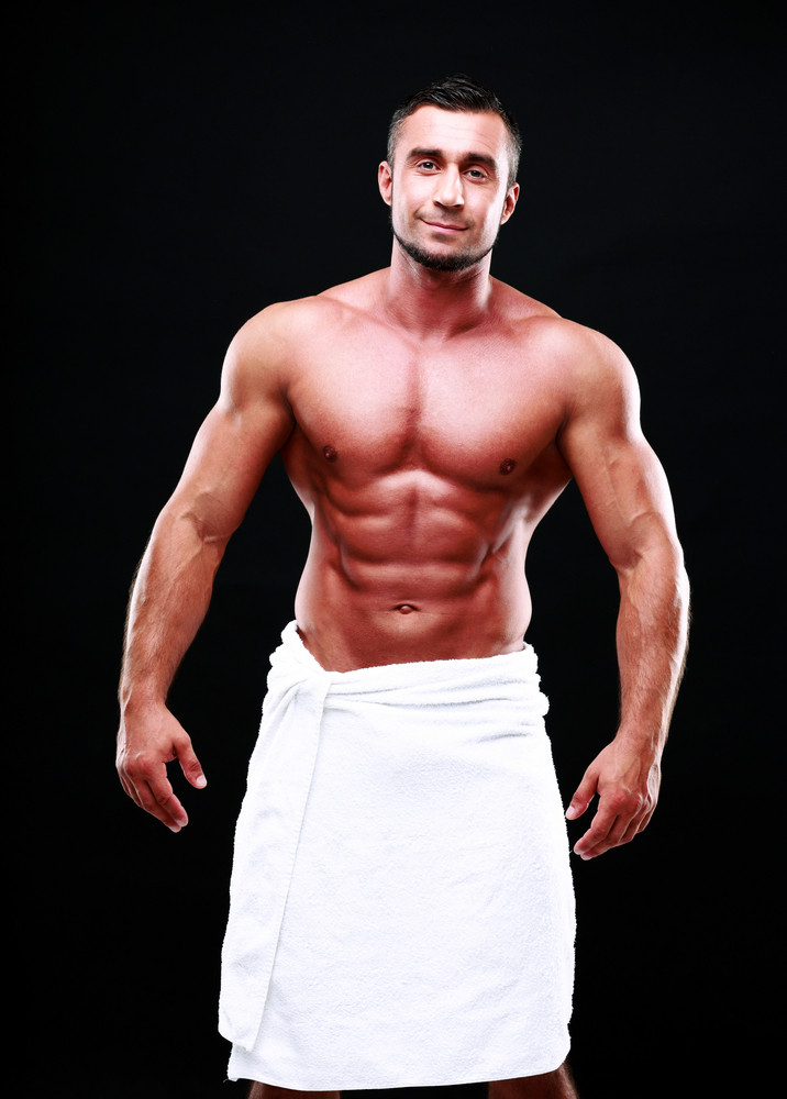 Happy muscular sportsman standing over black background