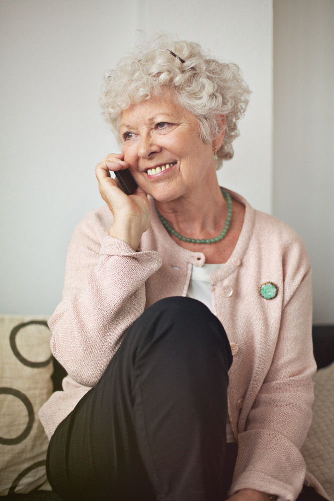 Happy senior woman with a cell phone sitting at home