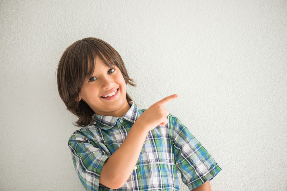 Happy smiling kid pointing his finger