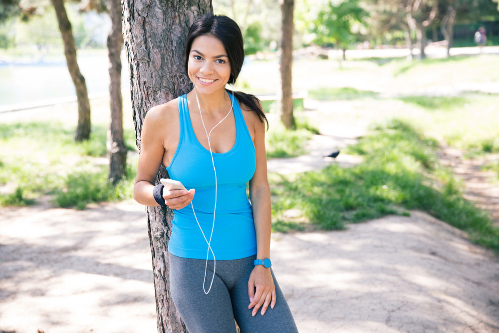 Happy sporty woman standing with smartphone outdoors