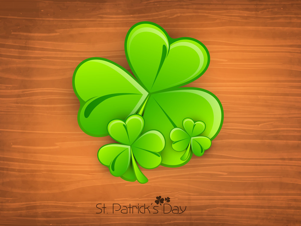 Happy St. Patricks Day Concept With Shiny Clover Leaves On Brown Background.