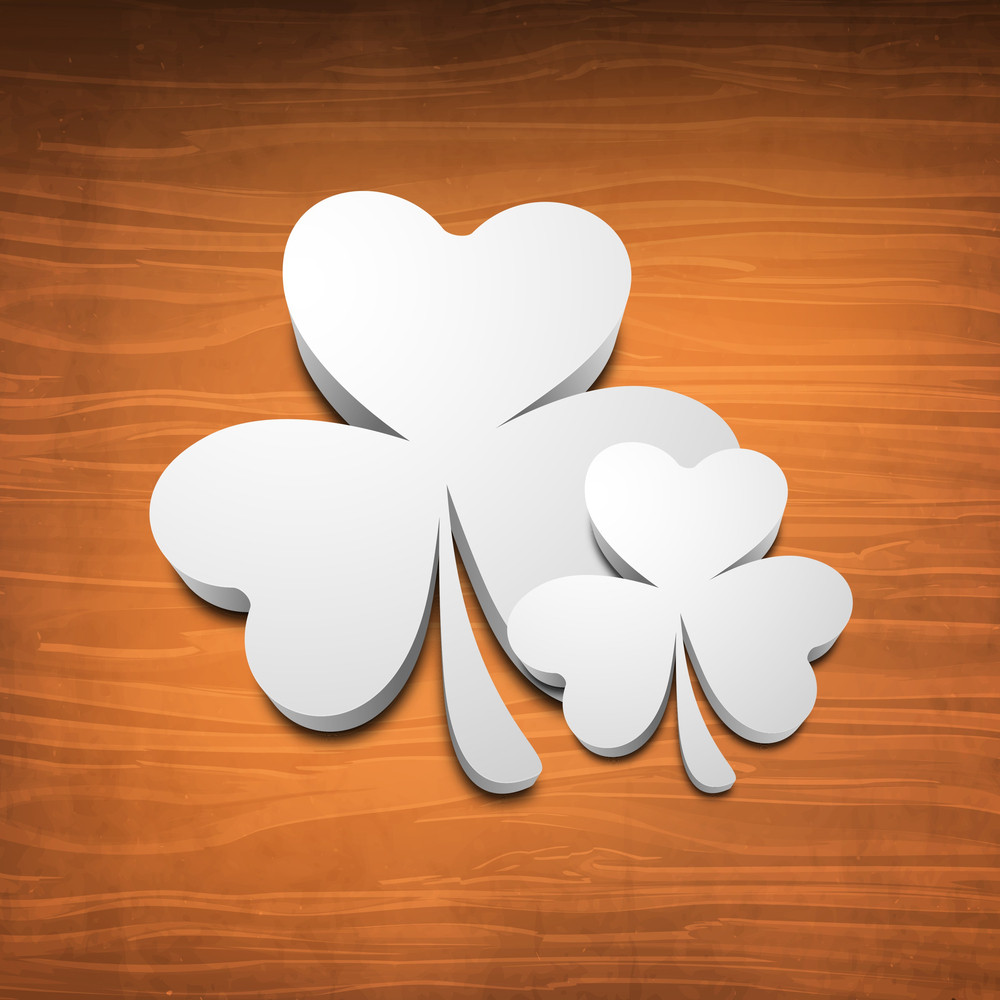 Happy St. Patrick's Day Concept With White Clover Leafs On Wooden Brown Background.