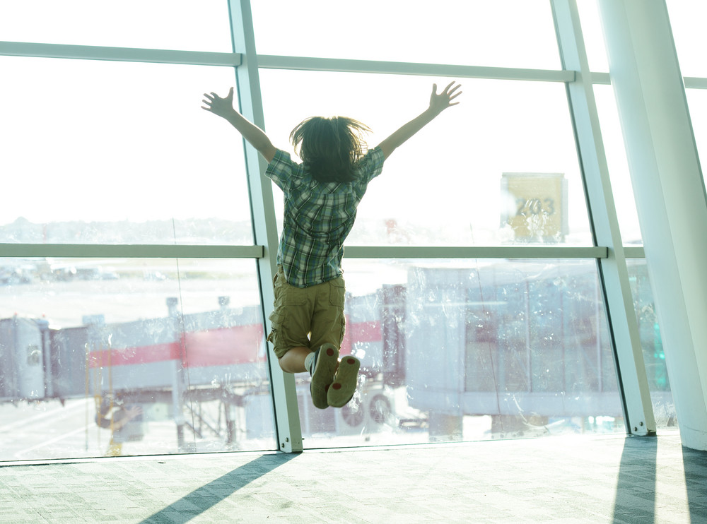 happy traveller boy jumping on airport waiting for airplane royalty