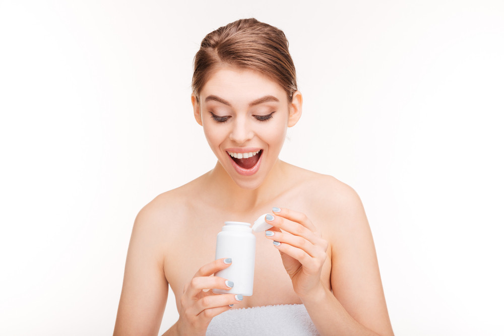 Happy woman holding bottle with pills isolated on a white background