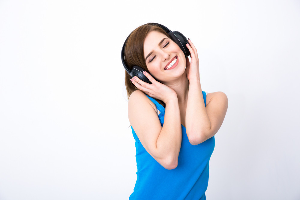 Happy woman with headphones listening music with closed eyes