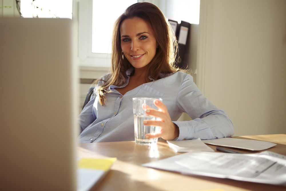 Happy young businesswoman sitting at her desk with a glass of water looking at camera smiling. Beautiful caucasian woman working from home office.
