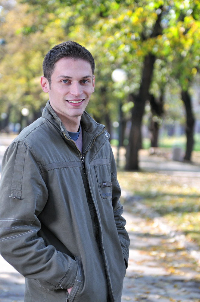 Happy young casual man outdoor portrait smiling