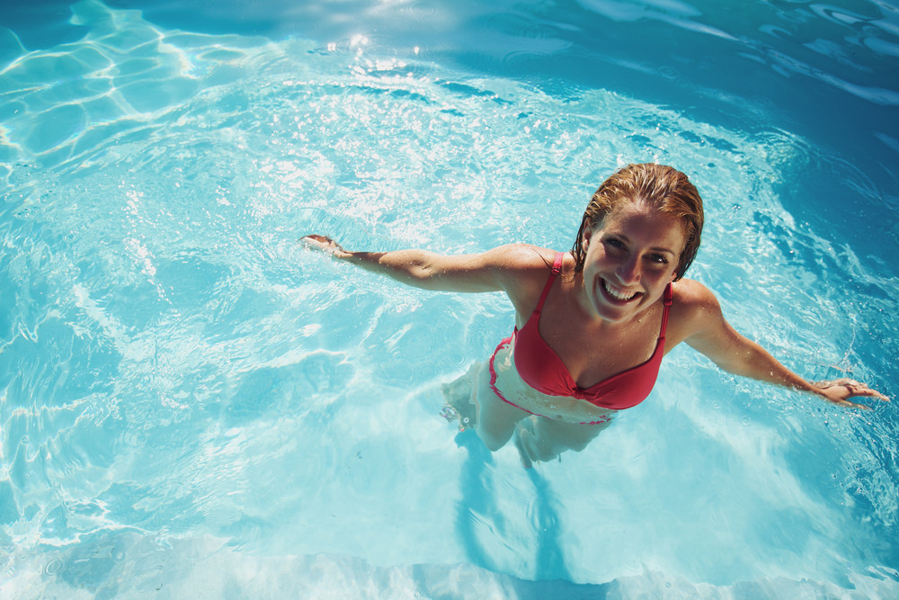Happy young girl relaxing in a swimming pool. Smiling young woman wearing swimwear standing in pool looking at camera.