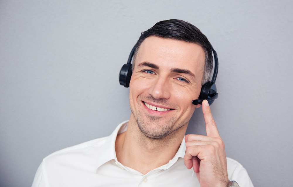 Happy young male operator in headphones