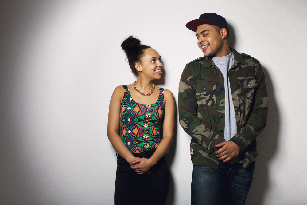 Happy young man and woman looking at each other smiling. Young couple in love against grey background.