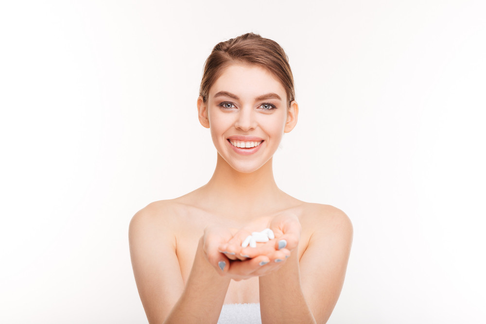 Happy young woman holding pill isolated on a white background