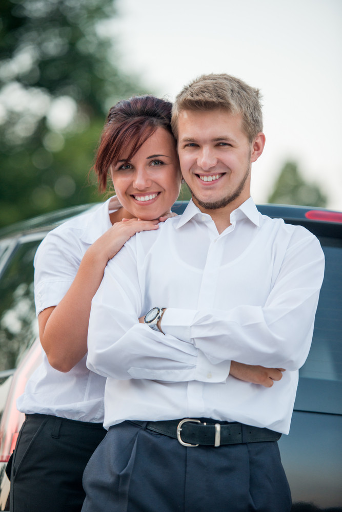 Happy young woman leaning on a man's shoulder posing by a car