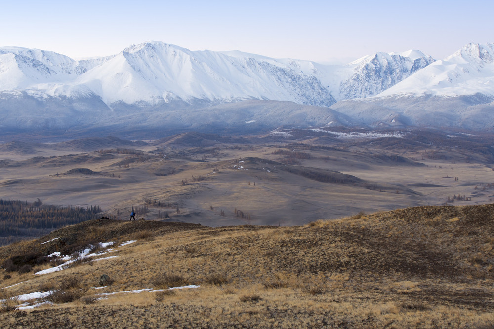 Hiker standing atop vast, rolling hills before snowy mountains