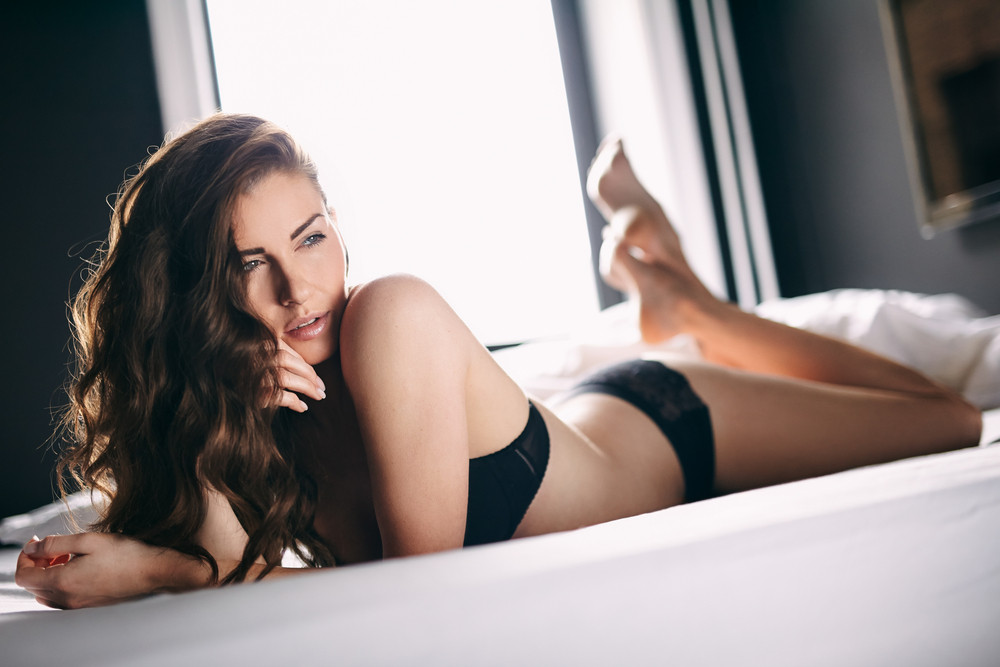 Horizontal shot of young female in black lingerie lying on bed looking away. Female in underwear daydreaming on bed.