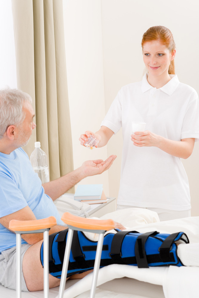Hospital - female nurse give pill to senior patient with broken leg