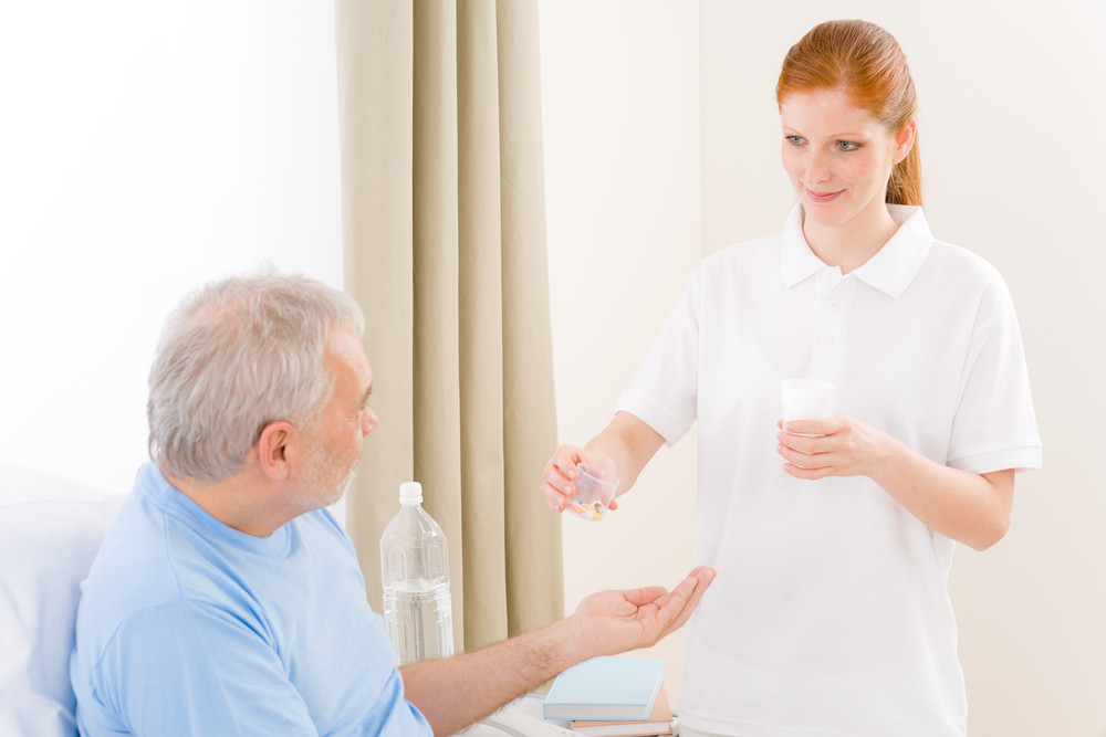 Hospital - female nurse give pill to senior patient