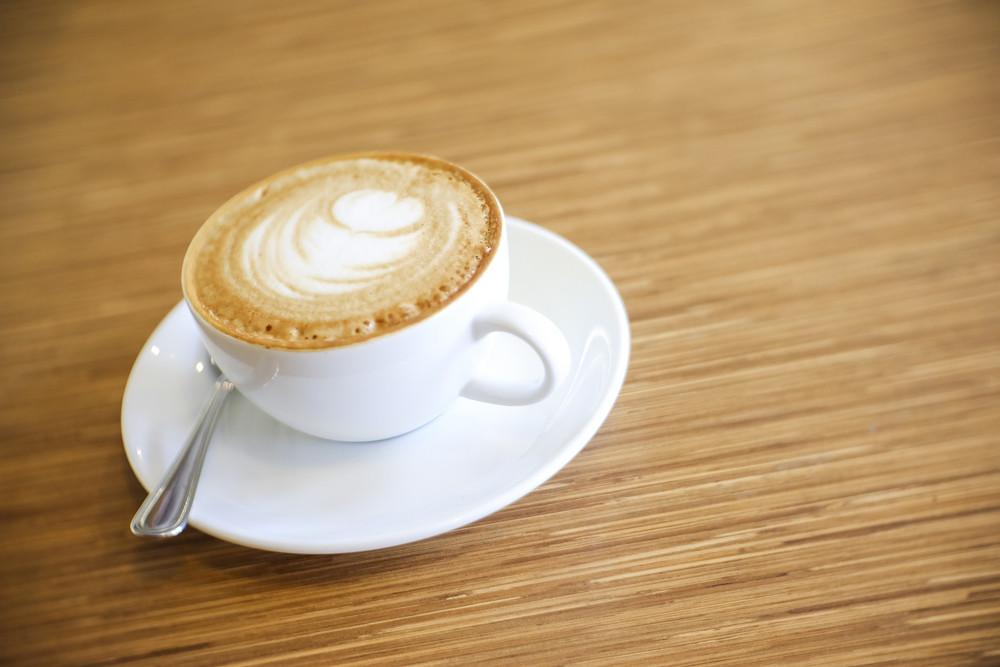 Hot Cappuccino with white cup on wood table coffehouse