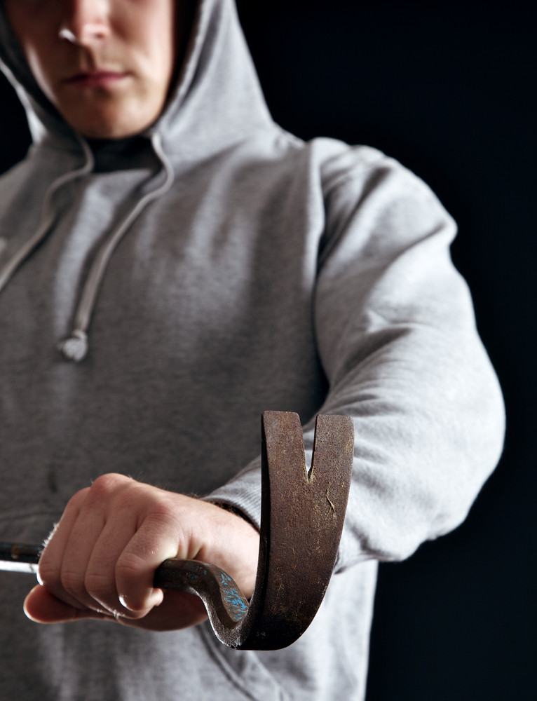 Housebreaker holding a crowbar ready to steal