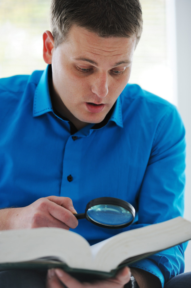 Image of a man  reading a book with magnifying glass