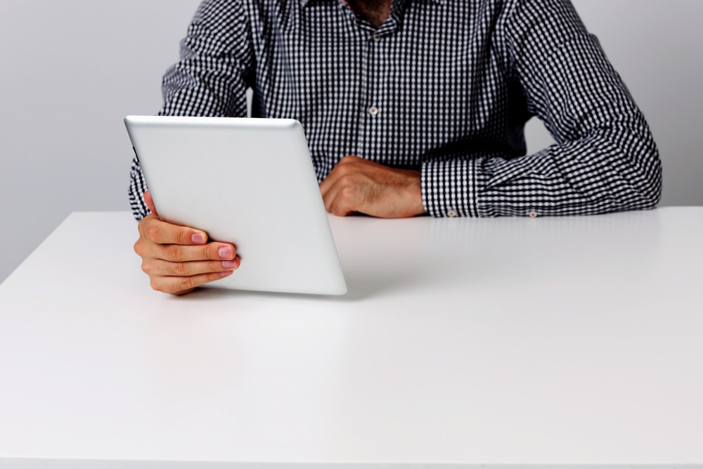 Image of a man sitting on the table and holding tablet computer