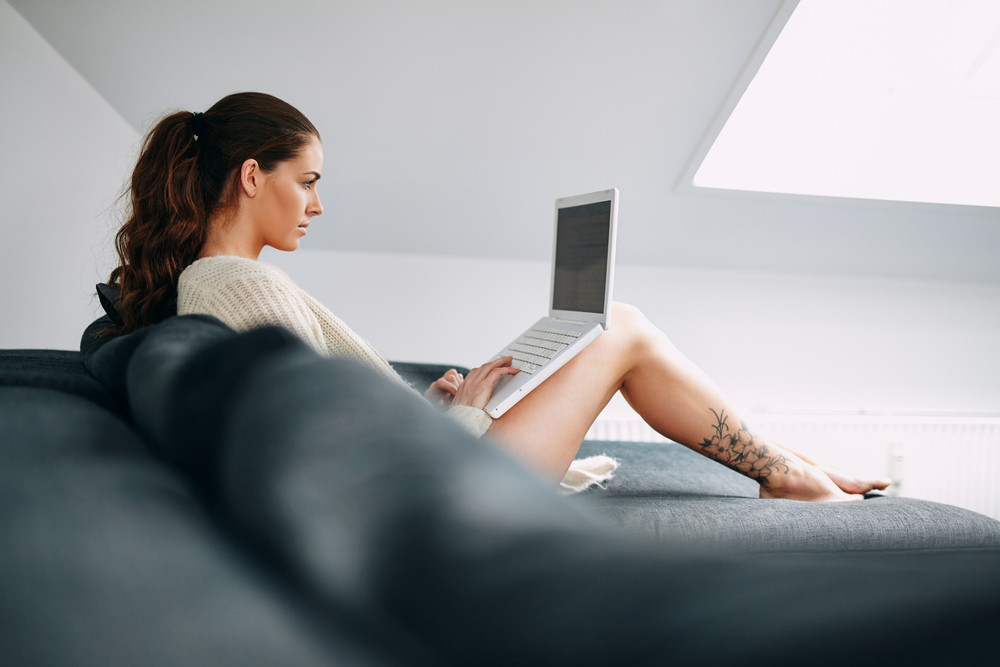 Image of pretty young brunette using laptop at home. Young female working on laptop while sitting on sofa.