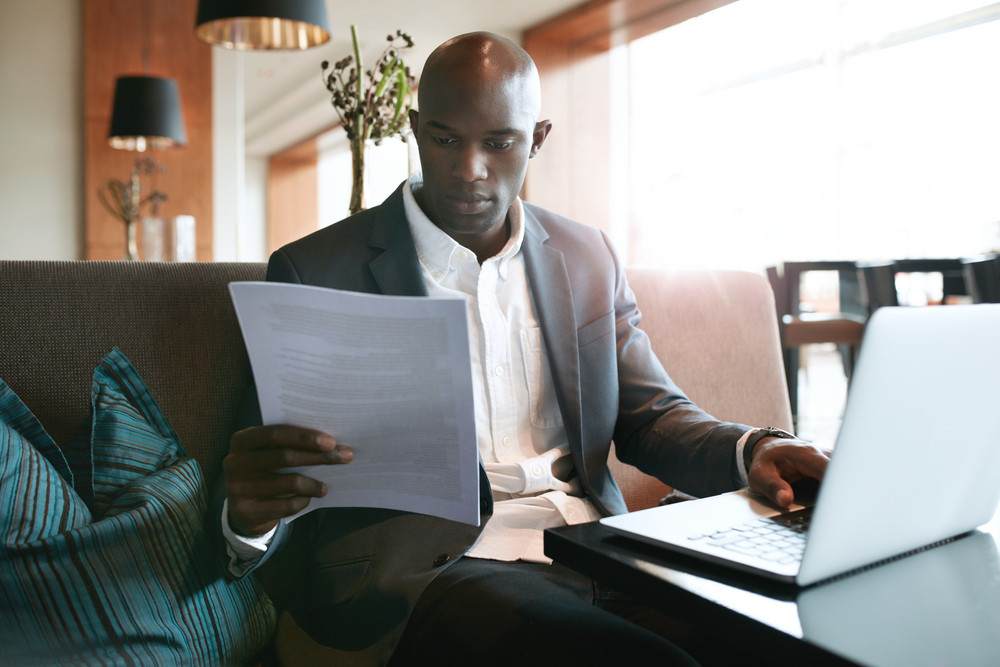Image of young businessman sitting a hotel coffee shop reading a document while working on laptop. Preparing himself for a meeting.