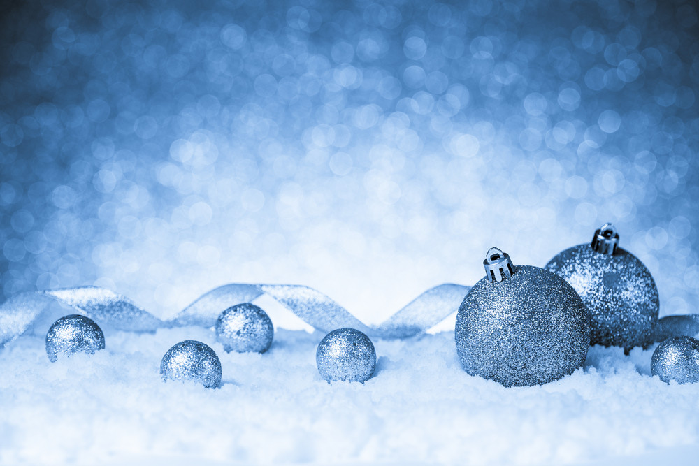 Christmas balls in snow on glitter background