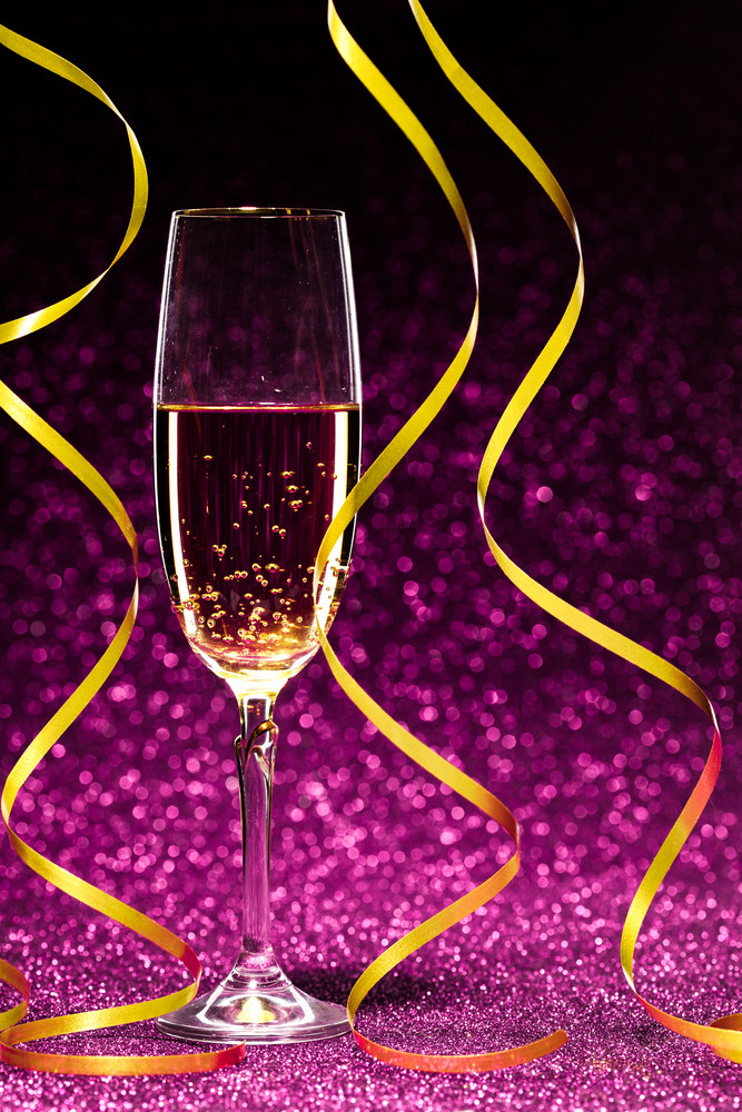 Glass of champagne with yellow holidays ribbons