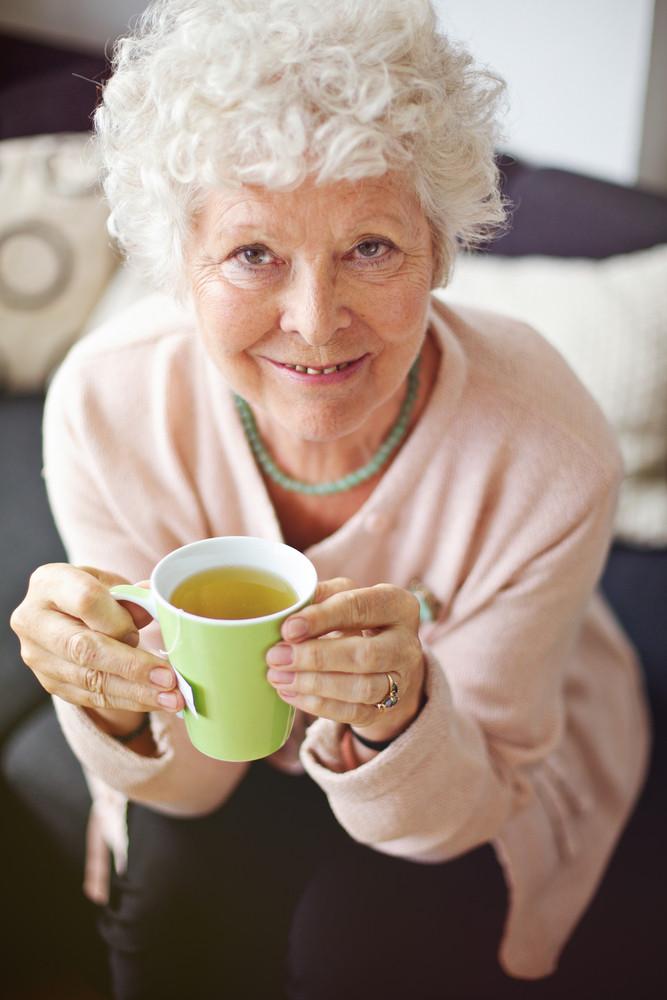 Indoor senior woman enjoying her tea and smiling at you