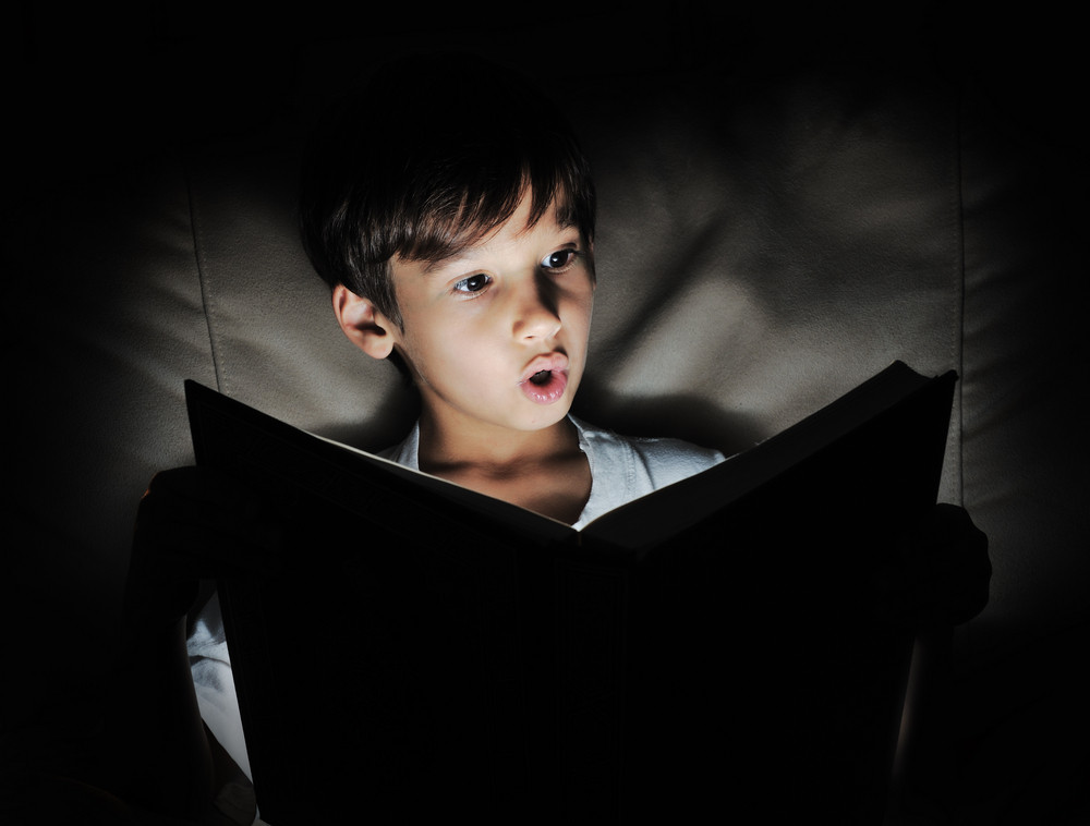 Kid reading book, light in darkness