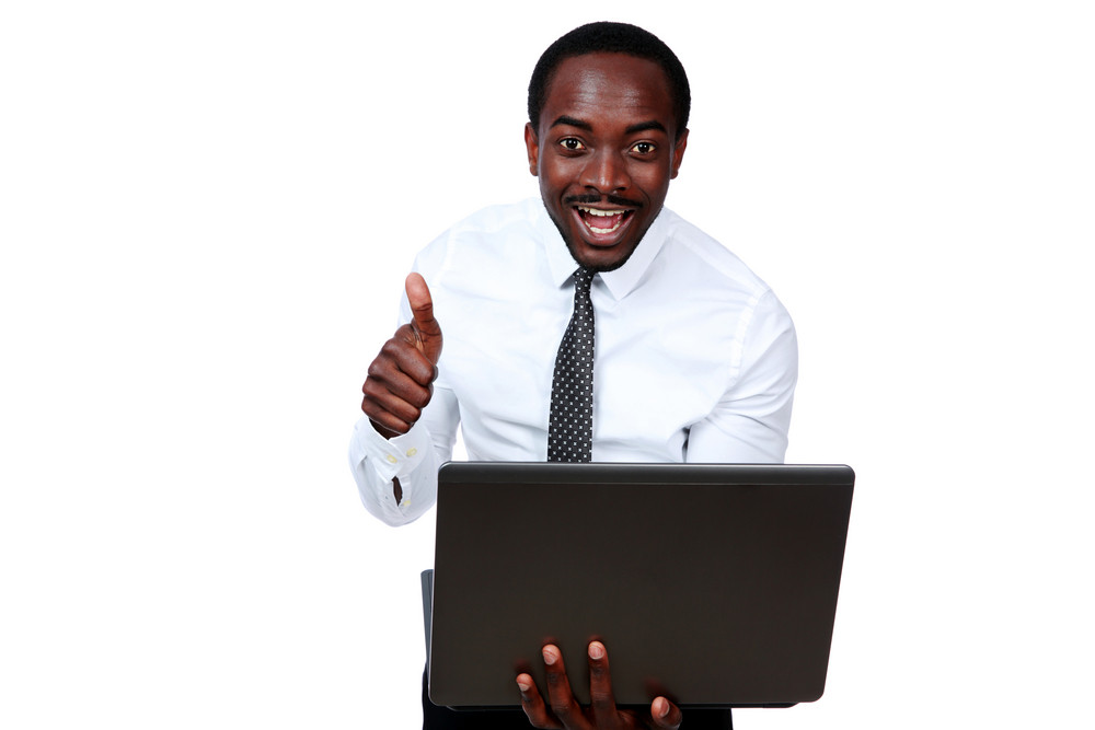 Laughing african man holding laptop and showing thumb up over white background