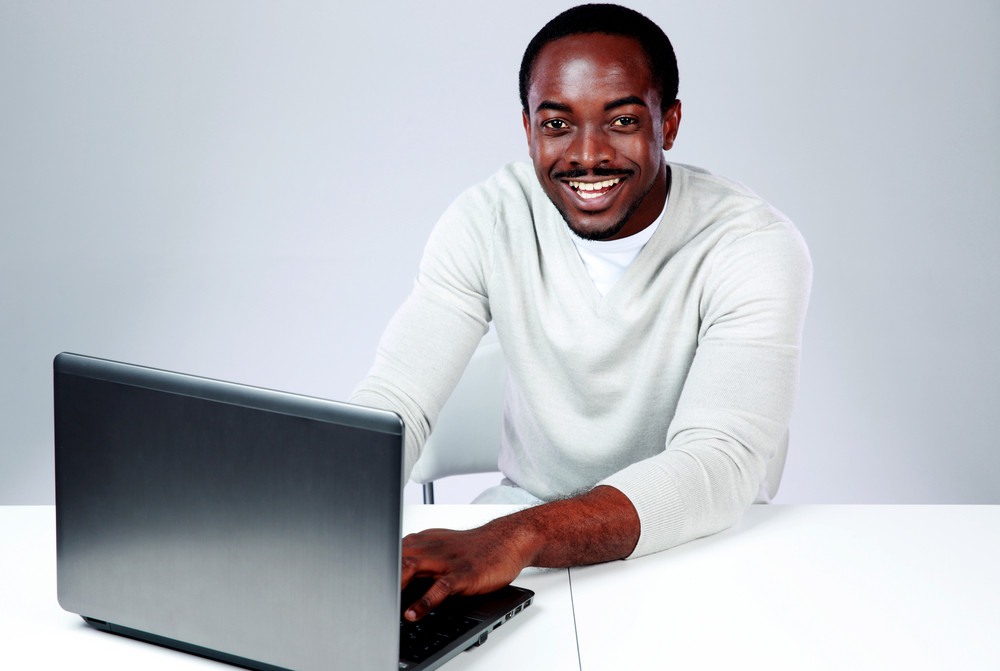 Laughing african man sitting at the table and using laptop on gray background