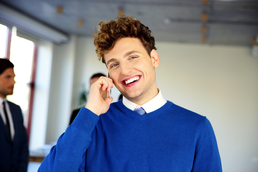 Laughing businessman talking on the phone in office