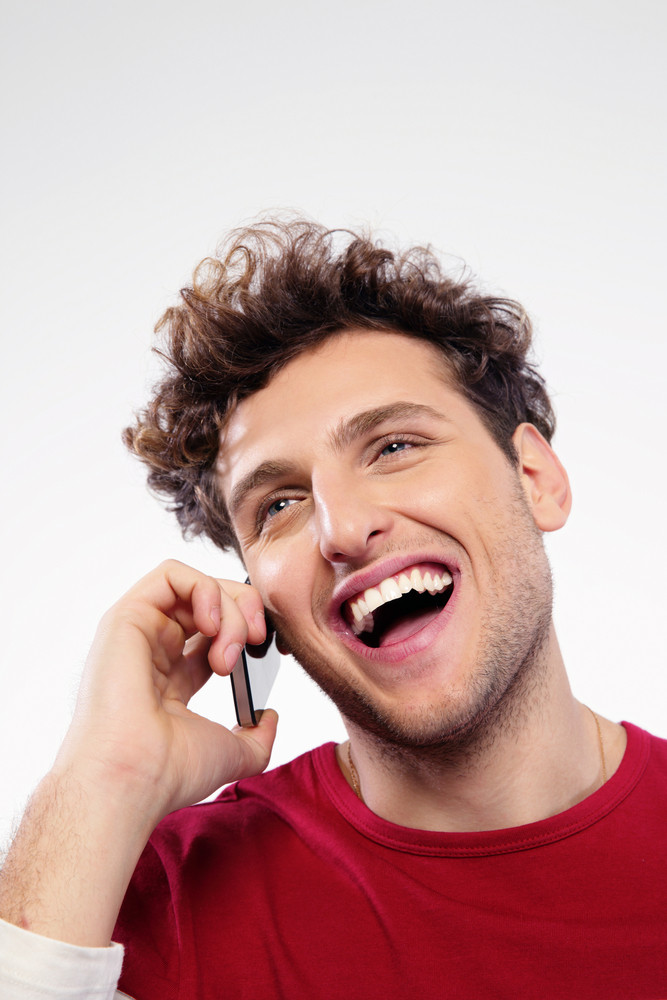 Laughing man with curly hair talking on the phone