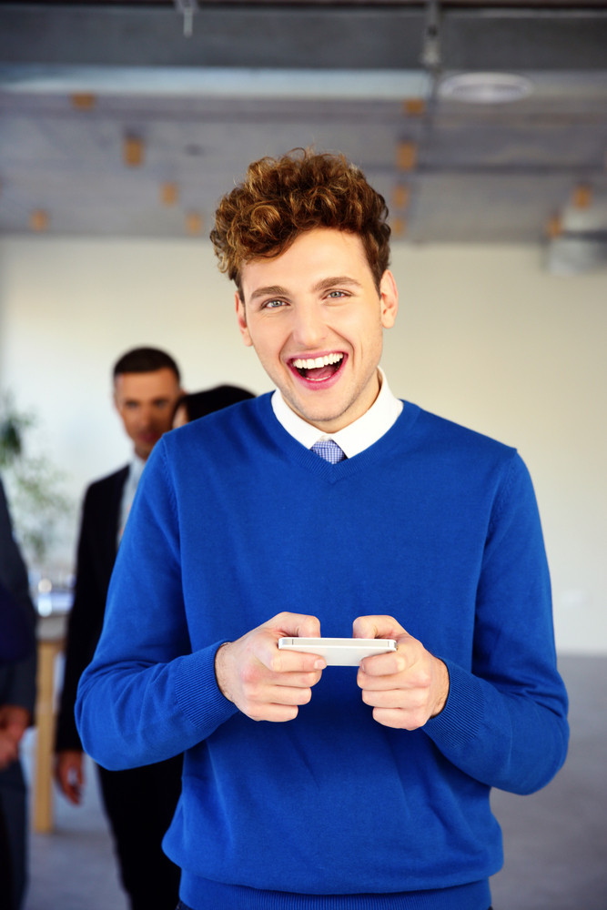 Laughing young businessman standing with smartphone in office