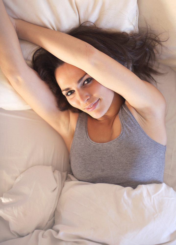 Lazy morning woman lying on bed stretching her arms