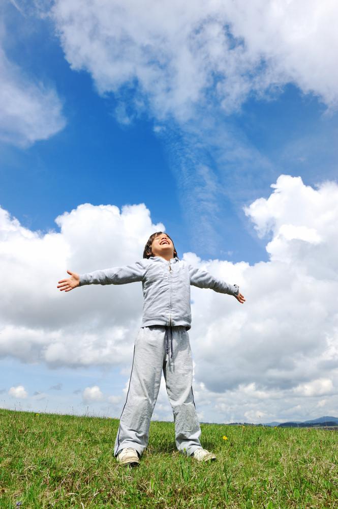 Little boy feeling a freedom on meadow in nature