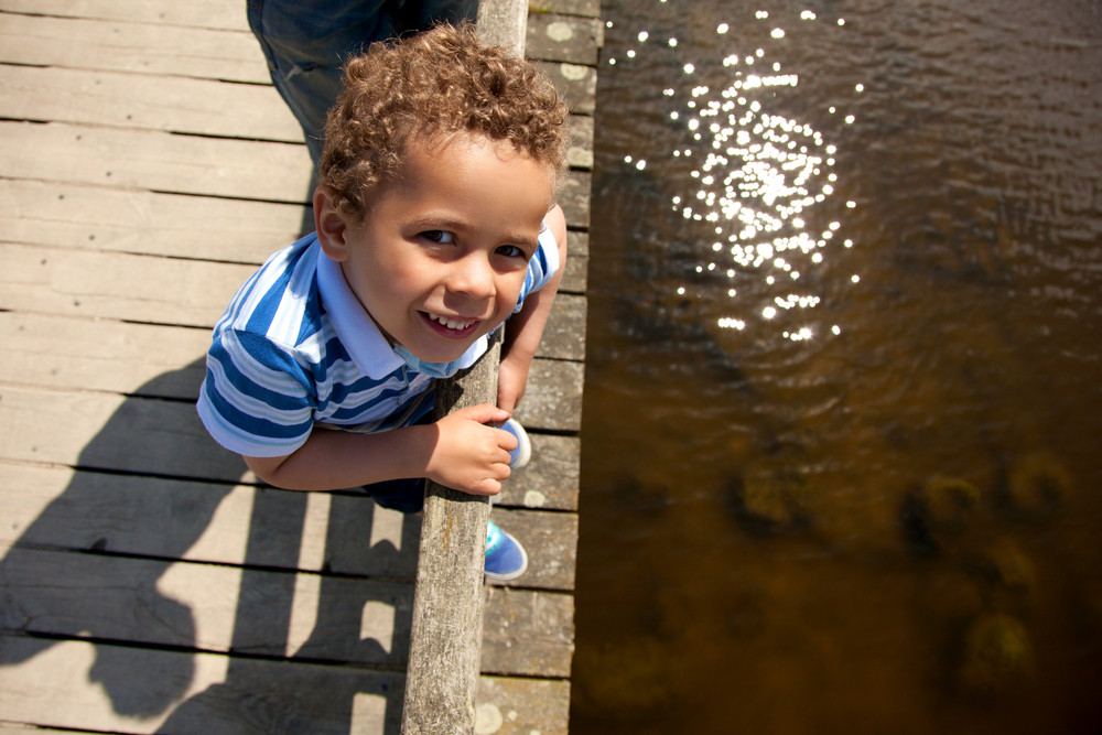 Little boy on a wooden bridge looking curious on a hot summer day
