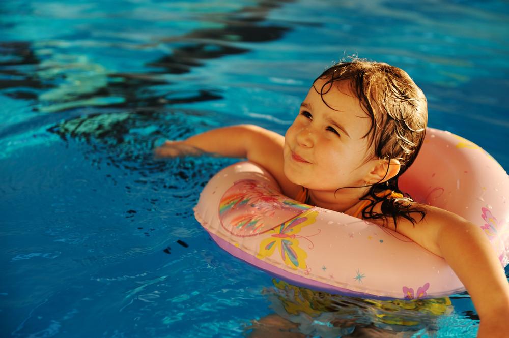 小可愛的女嬰在游泳池的水藍色,夏天的時候為了好玩