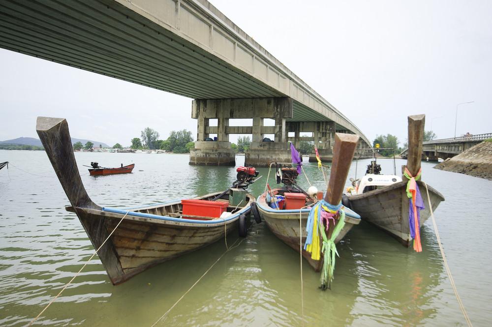 Long tail boat front of phuket bridge