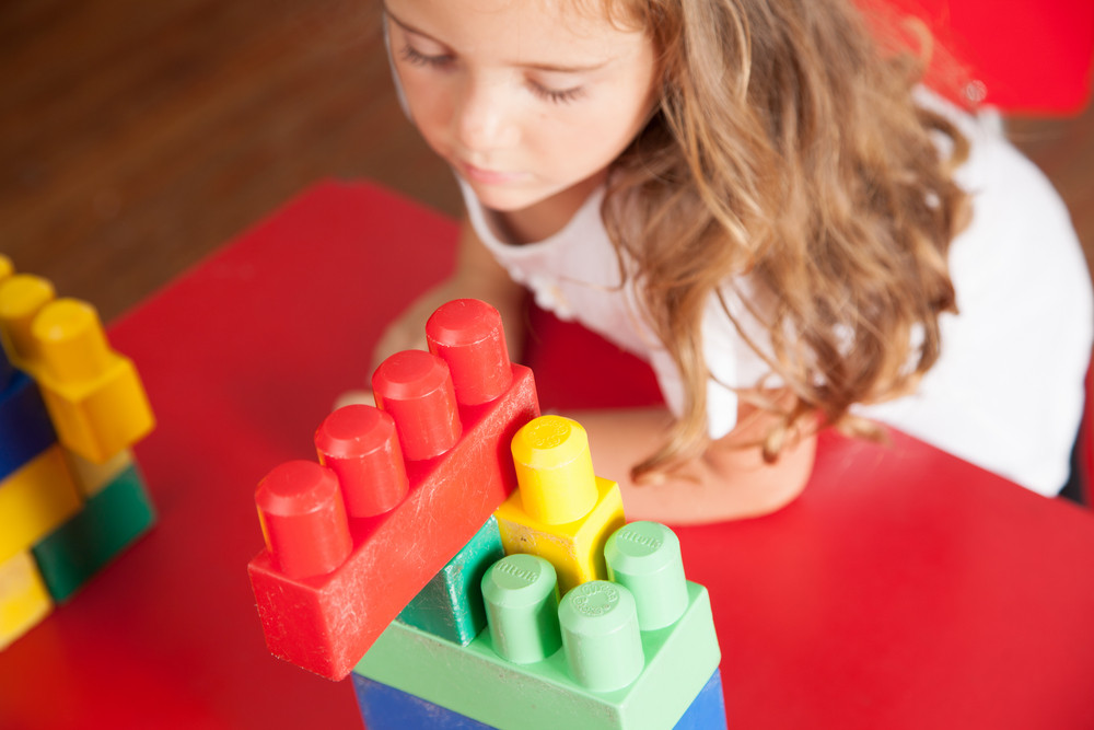 Lovely girl playing with blocks