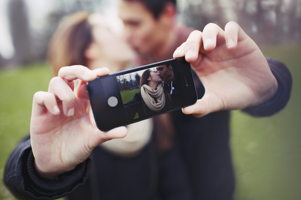 Loving young couple photographing themselves with a mobile phone while kissing at the park. Focus on smart phone.